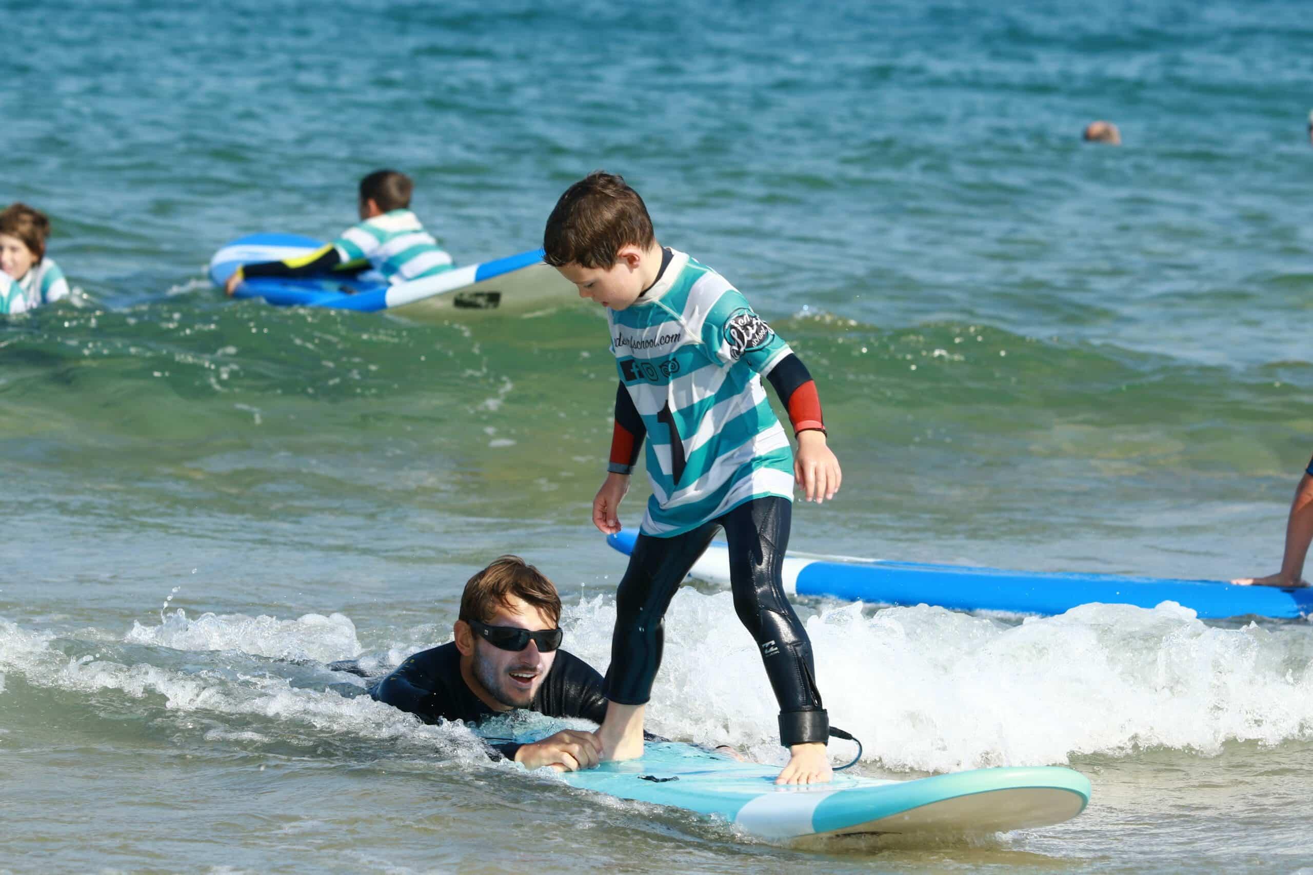 un moniteur aide l'enfant à prendre une belle vague