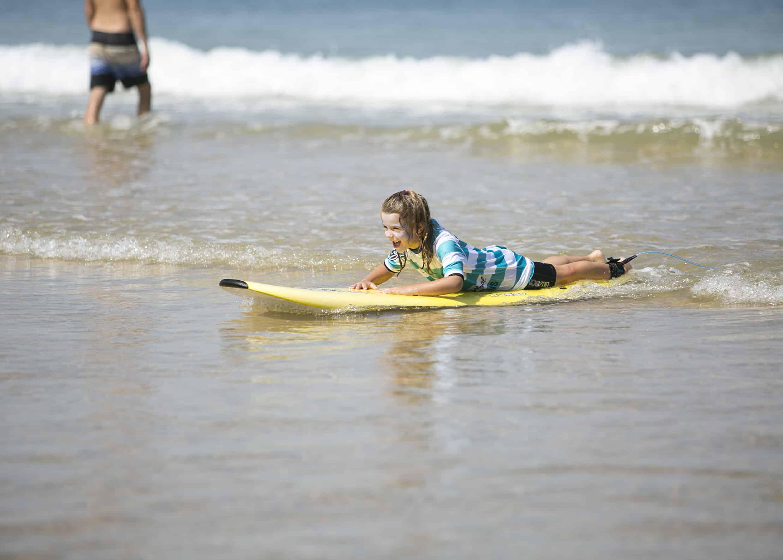 une enfant sourit et glisse sur une vague allongée
