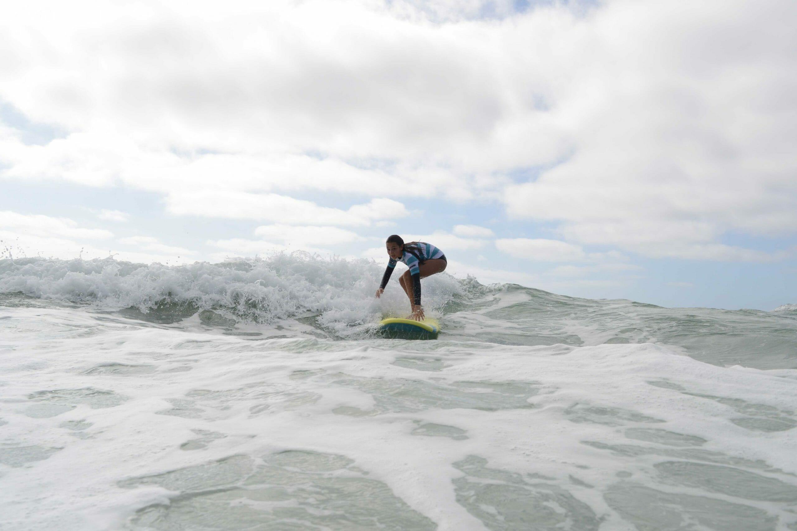 Une fille surfe une vague